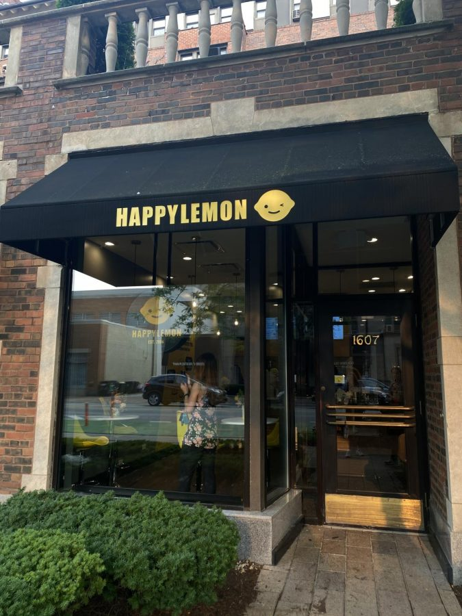 """The front of Happy Lemon with a black awning and yellow lettering spelling out """"Happy Lemon"""" with a yellow, smiling lemon next to it. Glass pane windows reflecting the outside of the store and bushes at the bottom left of the picture."""