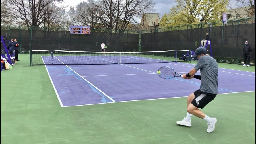 Northwestern men's tennis player wearing gray and black athleisure and white shoes returns a shot against Illinois.