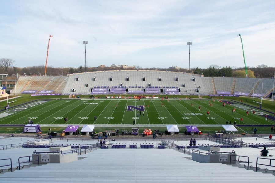 Gray stands rise up behind field with green grass and a giant N painted purple in the middle