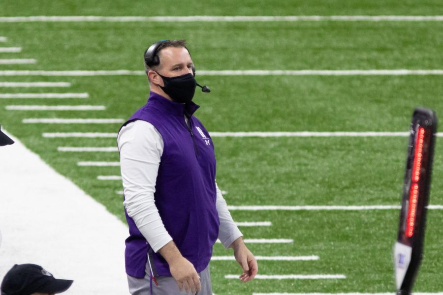 Man in purple fleece and white long-sleeved shirt with black mask and headset stands in front of green field with white lines and stripes.