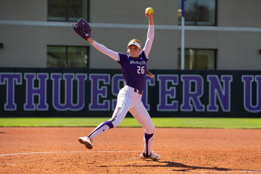 Northwestern softball player in purple uniform with arm raised prepares to pitch the ball.