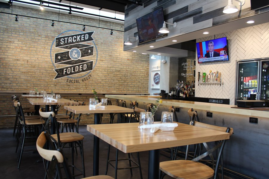 A row of wooden tables at Stacked and Folded, with a bar behind them and chairs facing each.