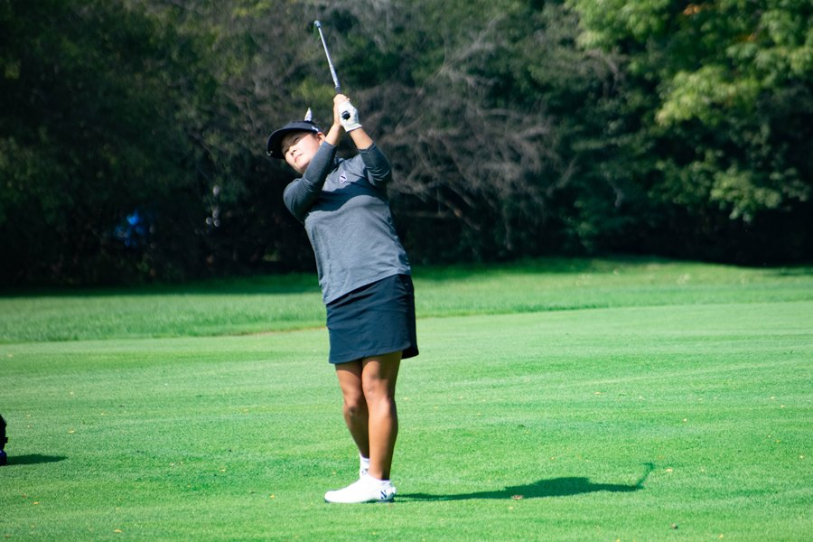 Golfer watches her swing against a green backdrop.