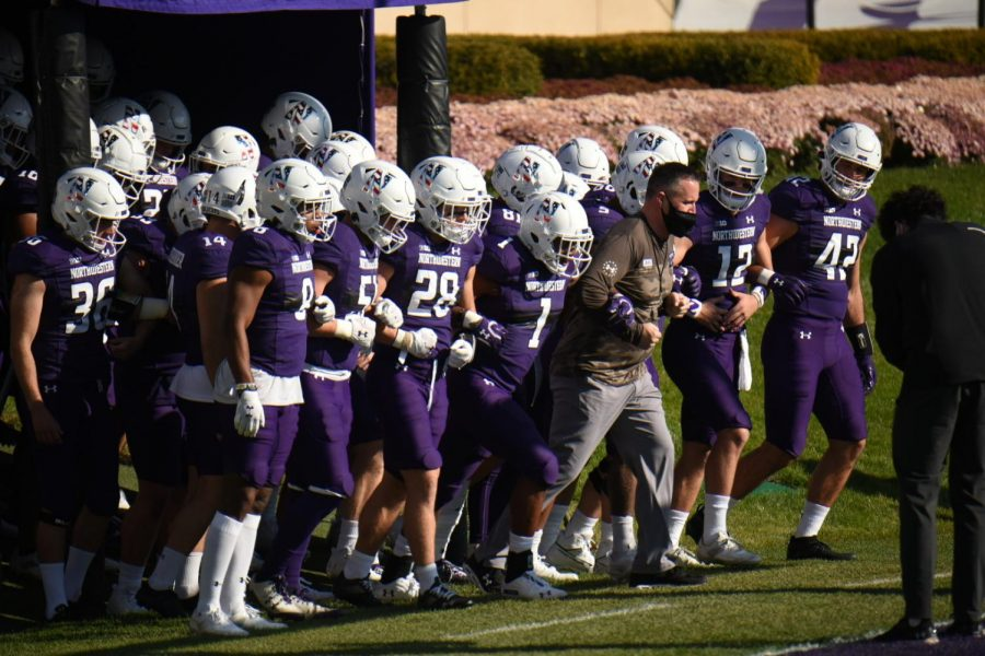 Players in purple uniforms are arm-in-arm as they walk out of the tunnel onto Ryan Field.