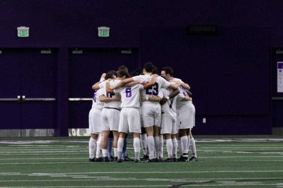 Northwestern players in white jerseys huddle together on green grass in front of a purple wall.