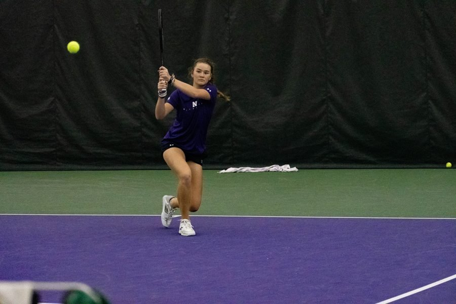 A female athlete in purple jersey and black shorts is holding a tennis racket, ready to swing at a green tennis ball on the tennis court.