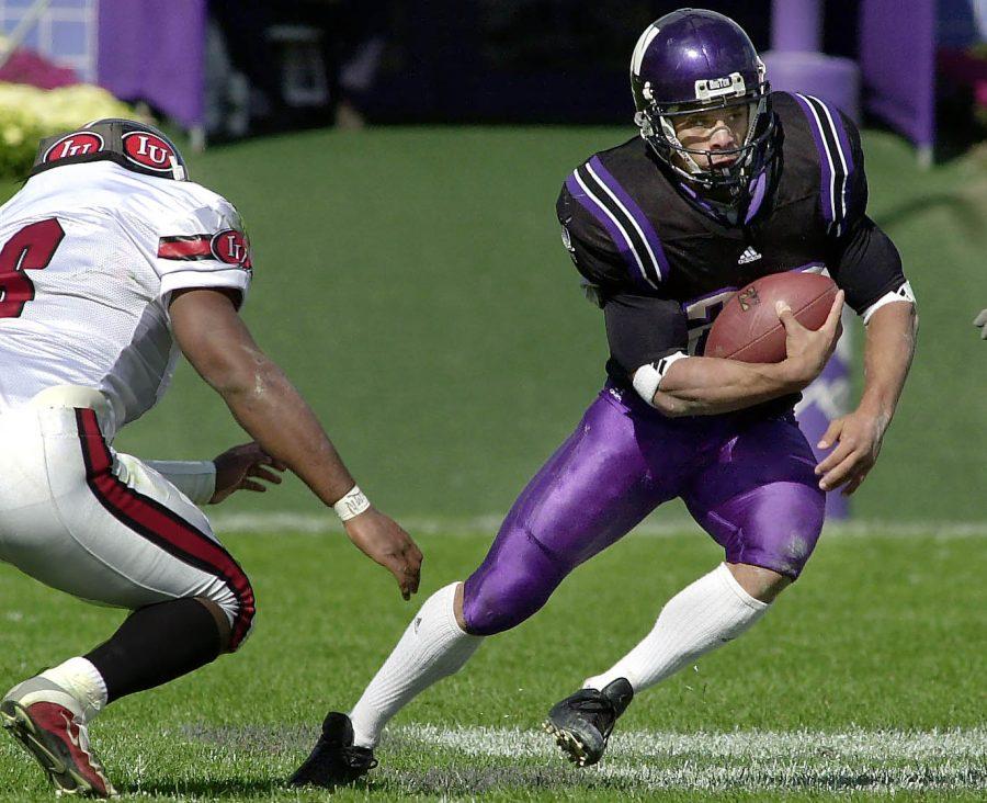 Football player evades opposing defenders.