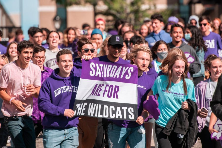 """Two students in purple shirts lead a crowd of other students as they hold up a flag reading """"Saturdays are for the Wildcats."""""""