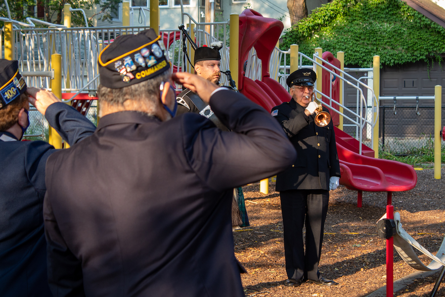 Two people wearing military caps salute. Behind them, another military member plays taps as a man wearing a bagpipe stands to attention.