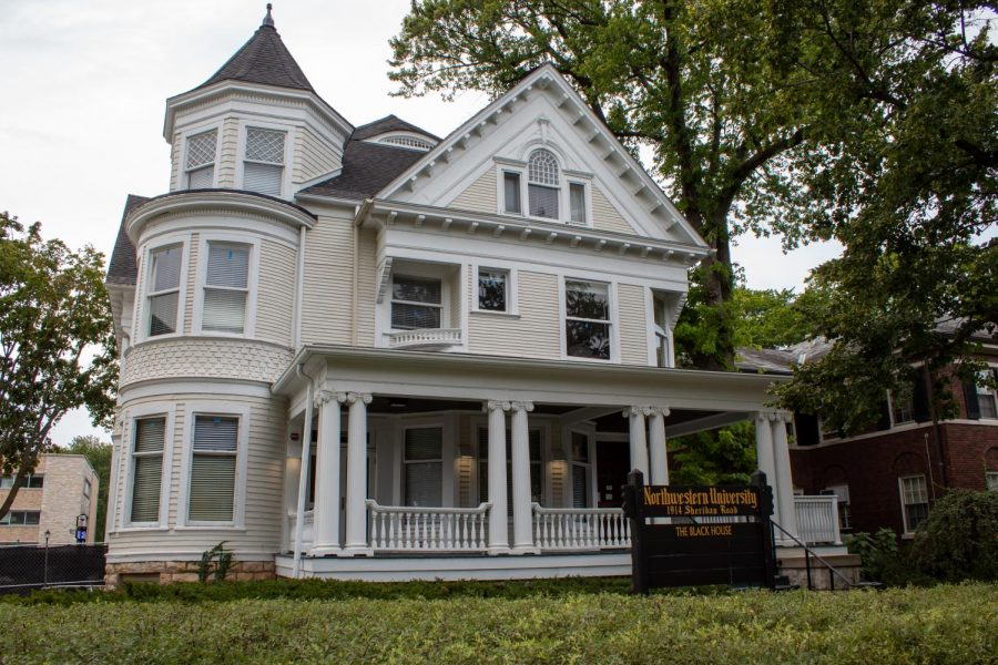 """An image of the Black House. The house is beige with a sign on the front porch that reads """"Northwestern University."""""""