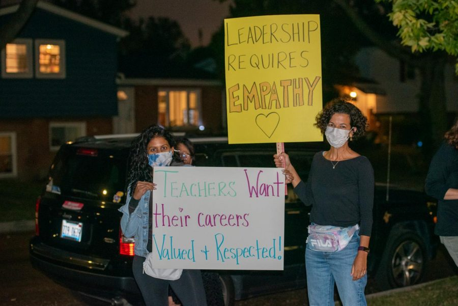 Two masked people stand side-by-side, outside at night, holding signs. One sign reads, Leadership requires empathy. The other sign reads, Teachers want their careers valued + respected.