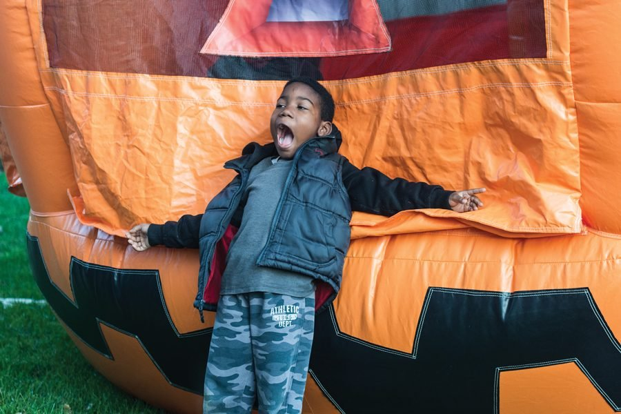 """A child stretches out his arms as leans against a giant orange inflatable pumpkins. His mouth is open as he exclaims """"""""The pumpkin is eating me!"""""""