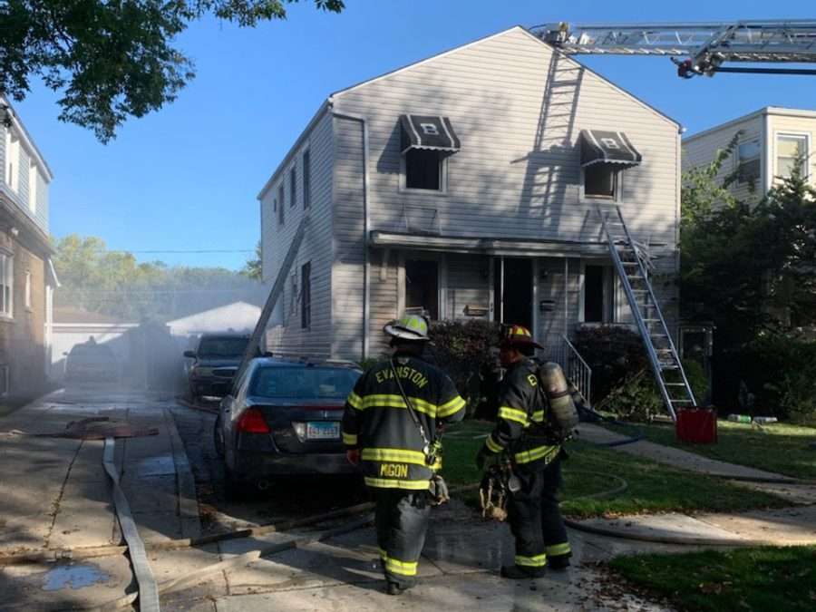 Two firefighters look toward a two-house on Foster Street. A ladder going up to an upper level window rests against the house.