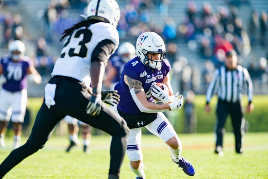 Player in purple jersey and white helmet holds football and turns towards player in white jersey.