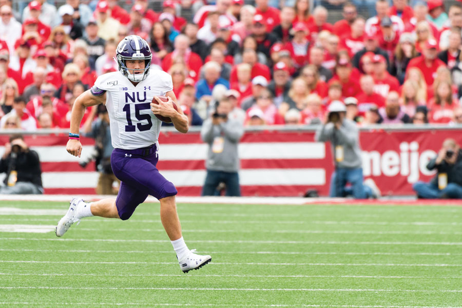 Hunter Johnson runs into open space on the football field, holding a football.