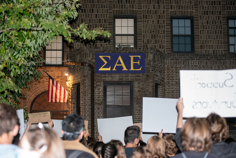 The Sigma Alpha Epsilon house, a large brick building with Greek letters on it. Protesters hold signs in front of the building.