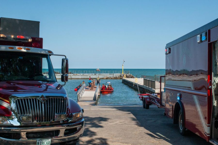 First responders stand on Church Street Power Boat Ramp. On each side of the ramp are small rescue boats. Evanston Fire Department trucks are parked on the road in front.