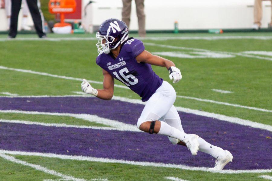 Player in purple uniform runs down field.