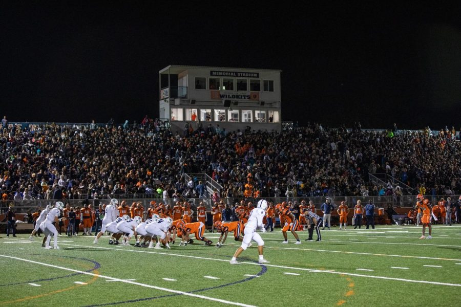 A high school football stadium sits behind two teams on the field in orange and white, preparing for the action to start.