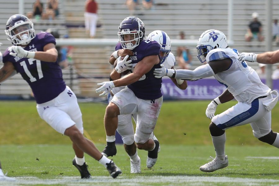 Player in purple uniform runs football