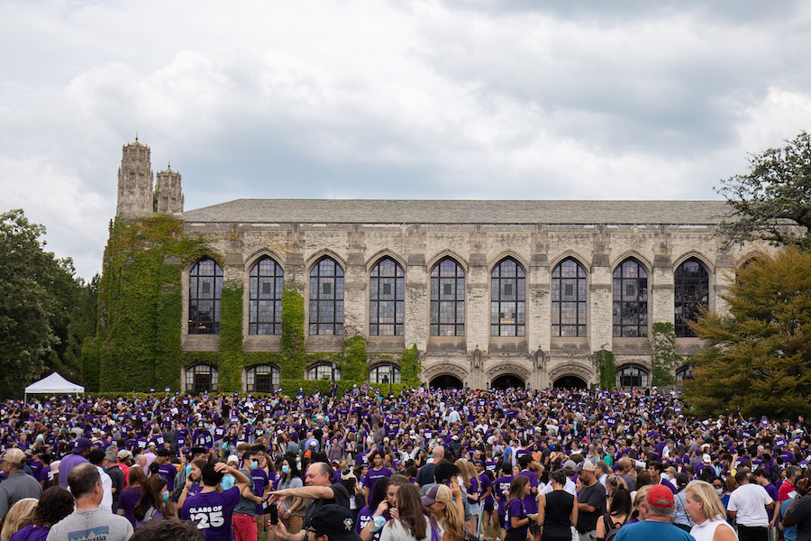 A large crowd of students from the Class of 2025 stand on Deering Meadow.