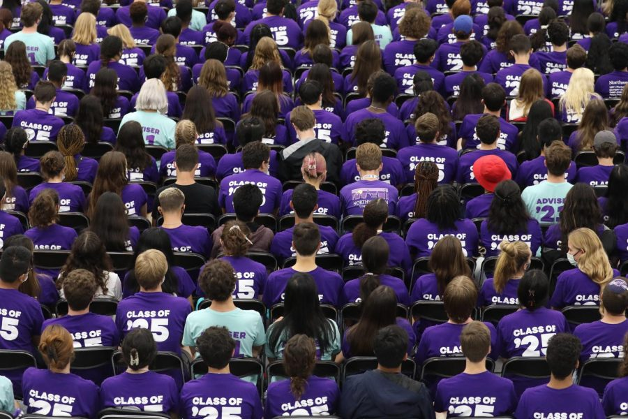 A large crowd of sitting students in purple and light green shirts face away from the camera.