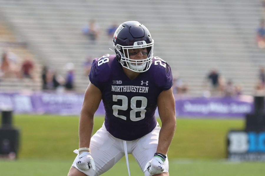 Player in purple uniform stands on field.