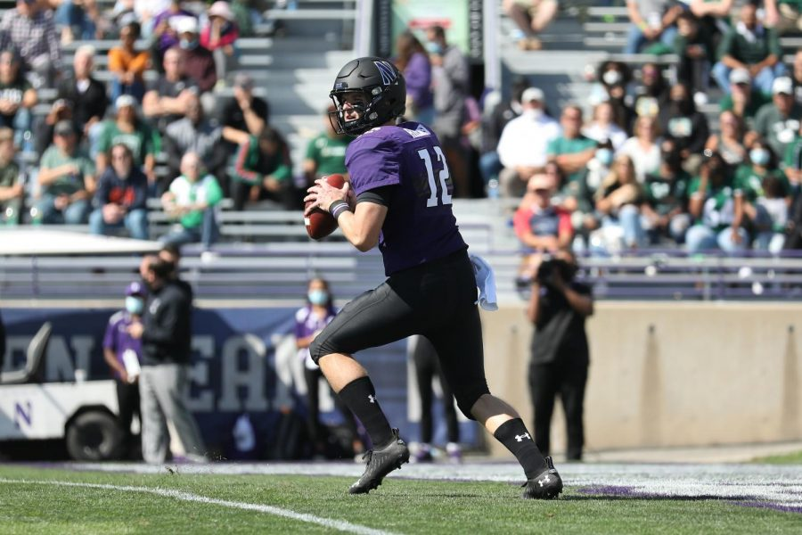 Purple player holds ball while running.