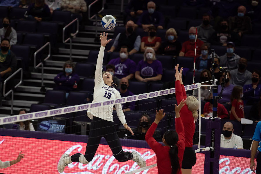 Volleyball player reaches up to hit the volleyball.