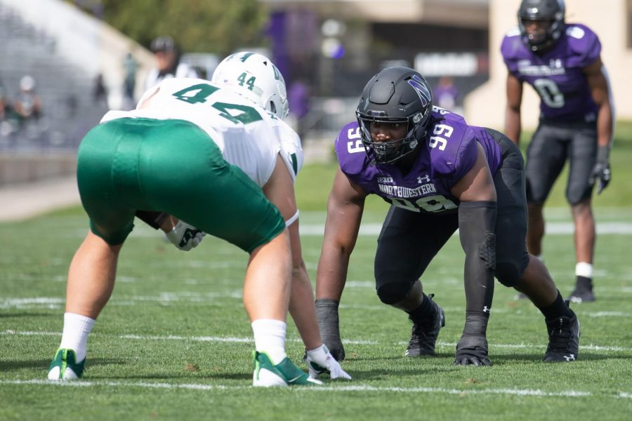Adetomiwa Adebawore lines up against an Ohio player before the snap