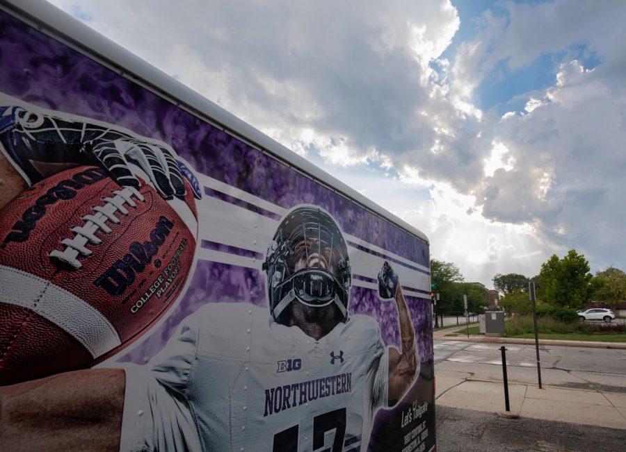A merchandise trailer outside a stadium features a football player flexing.