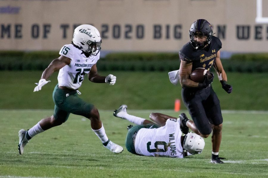 Northwestern football player runs while Michigan State football player pursues him.