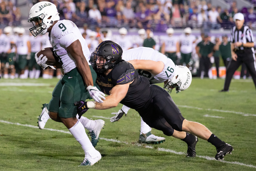 A Northwestern defenseman tries to tackle a Michigan State running back.