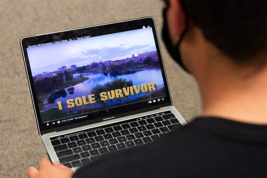 The+back+of+a+student+watching+a+YouTube+video+on+his+laptop.+The+screen+has+a+still+of+campus+with+the+words+%E2%80%9C1+Sole+Survivor%E2%80%9D+written+across+the+bottom.