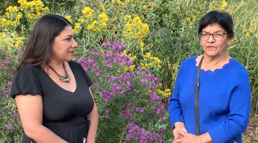 Two women with brown hair standing in front of yellow and purple flowers. The woman on the left is wearing a necklace and a black dress with short sleeves, and the woman on the right is wearing glasses and a blue dress with long sleeves.