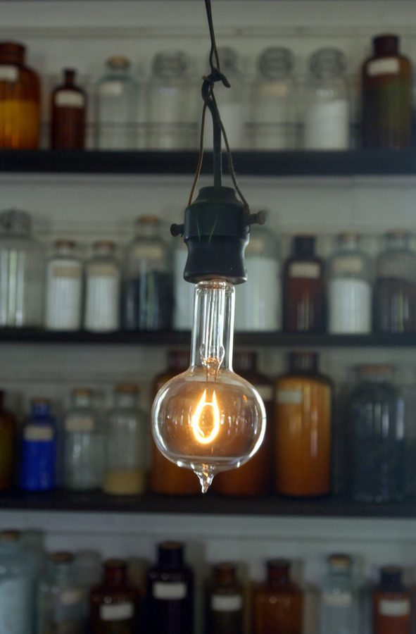 A single illuminated, industrial lightbulb hangs from the ceiling.