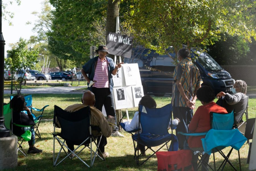 """There is a black poster board with the words, """"We Walk: Black Internationalism"""" Underneath are various printed slides with photos of people and information. A person stands next to the poster, which is leaning against a tree, and speaks to a group of people sitting in lawn chairs."""