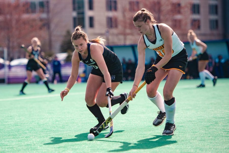 Girl with long brown hair in ponytail in black bends down with field hockey stick in hand