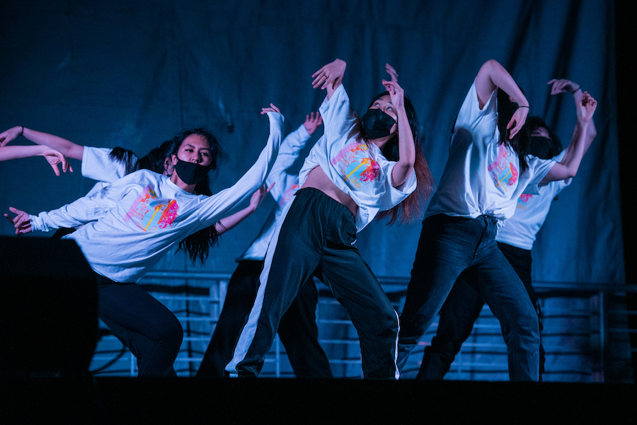 Three dancers lean to the side in a line, their arms creating a continuous wave. Another line of dancers do the same behind them