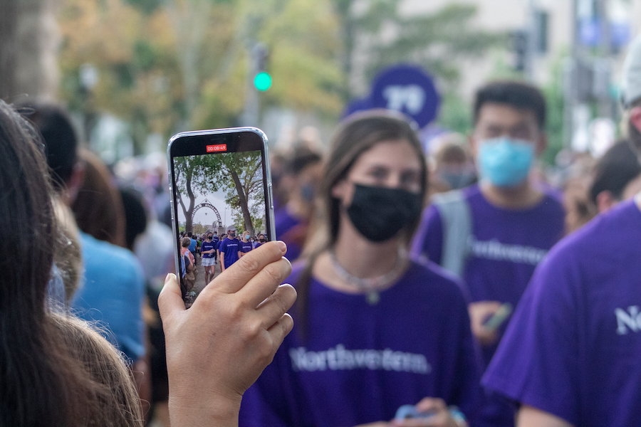 An observer records the March through The Arch. Students dressed in purple can be seen on the screen of the phone as they pass under The Weber Arch.