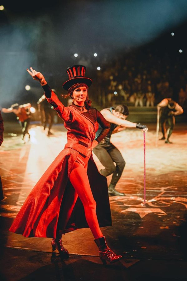 """""""Let's Get Wicked"""" actress Annabel Forman, seen in a red dress and top hat, raises her arm in performance in front of background dancers."""