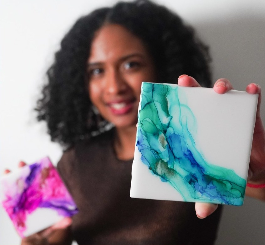 Artist poses in front of a white backdrop and holds up two examples of her watercolor-patterned alcohol ink coasters, one teal-and-blue and one purple-and-pink.