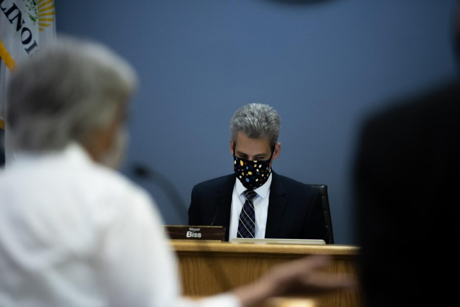 Mayor Daniel Biss looks down while sitting at his desk.