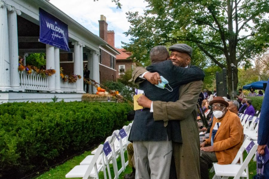 Two men hug in the front lawn of the Black House. They are standing in front of rows of white folding chairs.