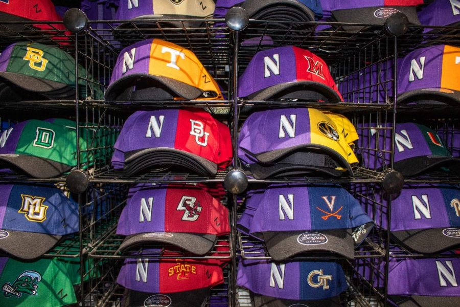 An arrangement of baseball hats that are purple and a variety of other colors representing Northwestern and other colleges.