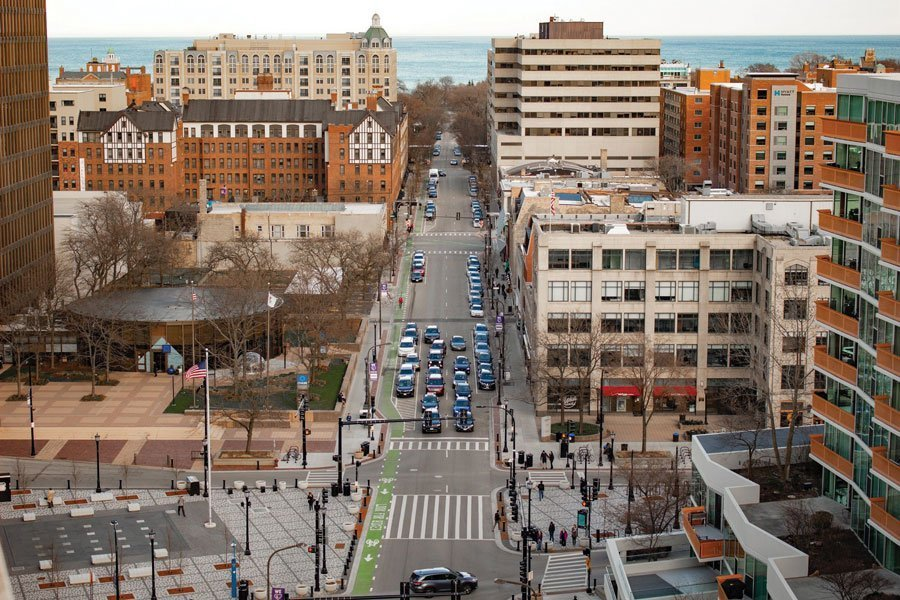 An aerial view of Evanston shows a street lined with over 20 cars and multiple large buildings on both sides with Lake Michigan in the background.