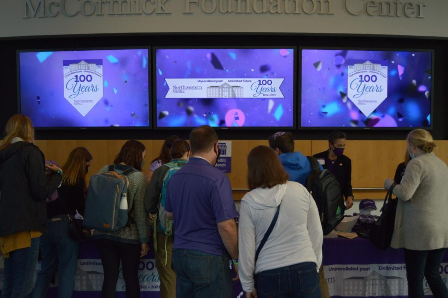 People standing in front of a table and TV screens with Medill 100 years logos.
