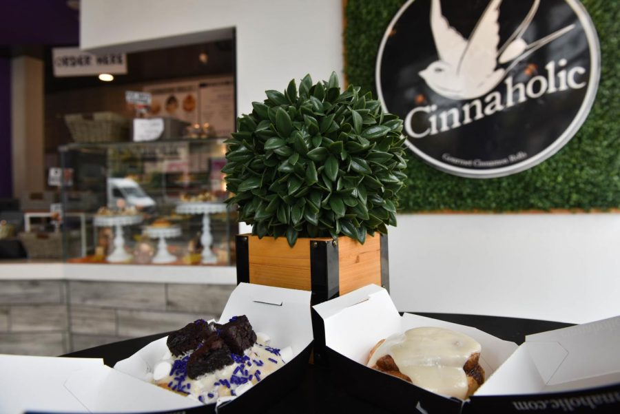 Cinnamon roll is held in front of the Cinnaholic storefront in Evanston.