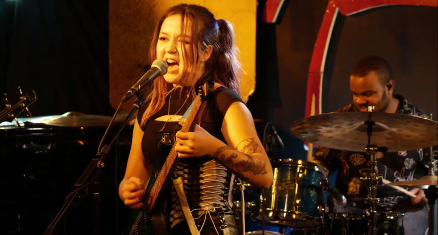 A woman sings into a microphone while playing a guitar in a club. In the background, there is a man on the drums.