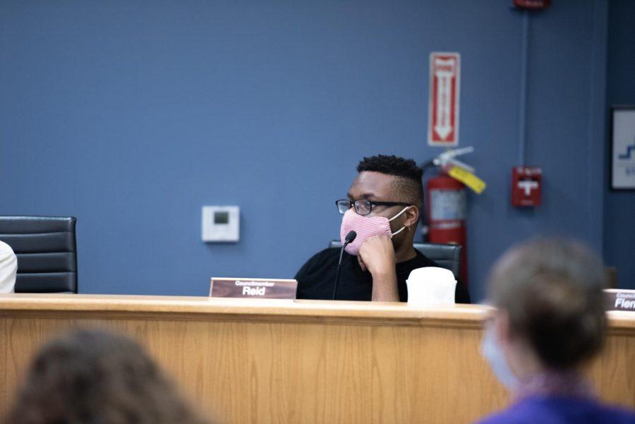 Councilmember Devon Reid (8th) sitting at a City Council meeting.